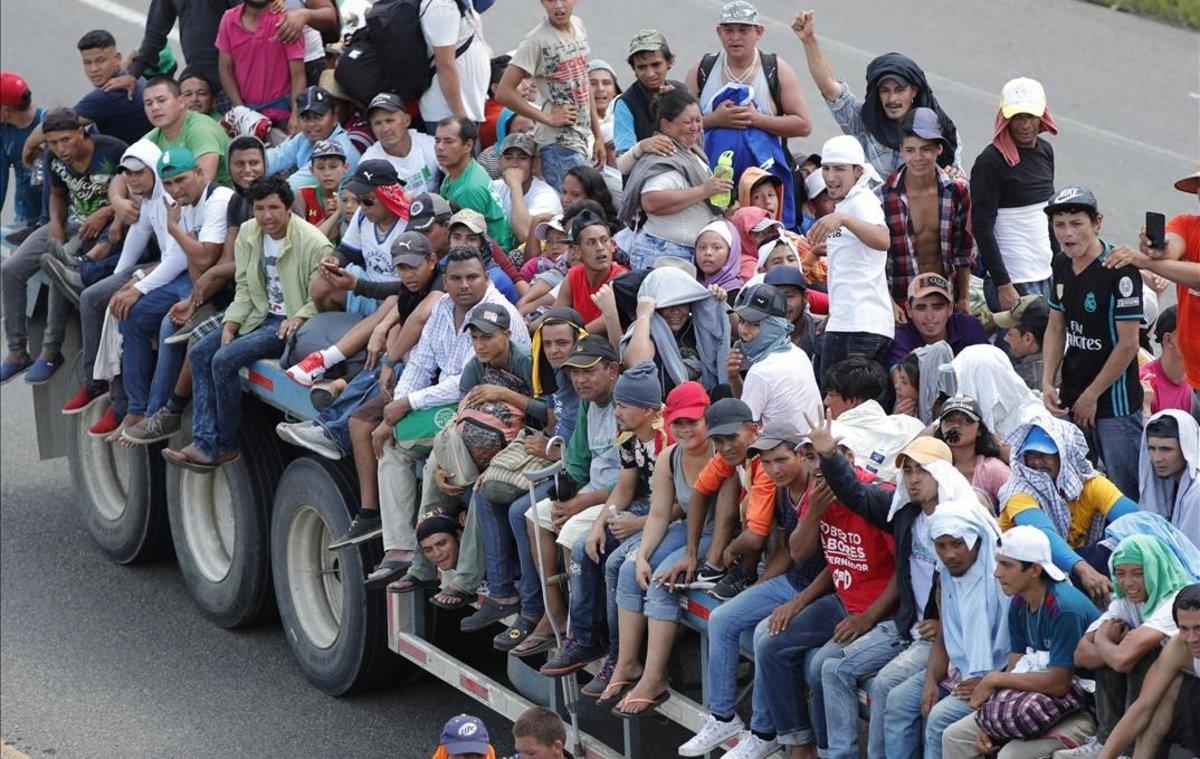 Migrantes hondurenos suben a vehiculos que se encuentran en el camino para continuar otro tramo del territorio mexicano rumbo a su objetivo principal, Estados Unidos.