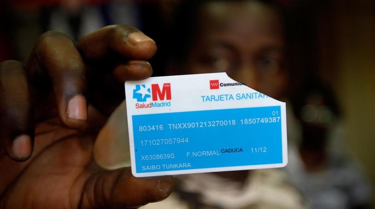 Un inmigrante muestra una tarjeta sanitaria rota.
