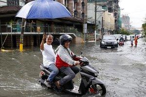 Un motorista maniobra en una calle inundada de Manila.