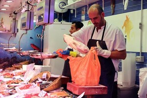 Un pescadero coloca productos en una bolsa de plástico en un mercado barcelonés.
