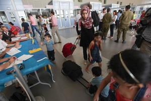Palestinos con doble nacionalidad abandonan Gaza en el puesto fronterizo de Erez, este domingo.