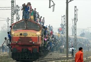 Pasajeros colgados de un tren en las afueras de Nueva Delhi, India