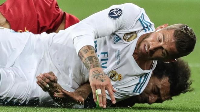 Sergio Ramos cae sobre Salah tras la disputa de un balón y le lesiona.
