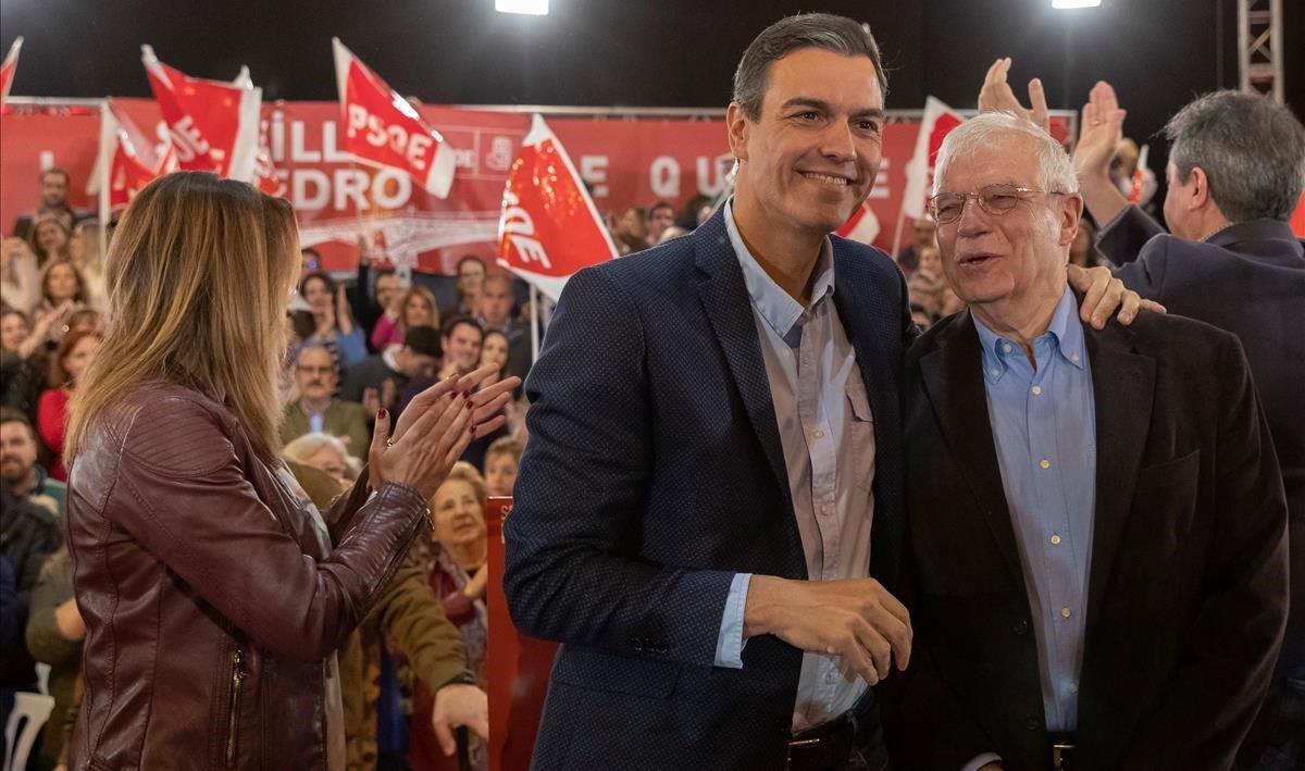 El presidente del Gobierno, Pedro Sánchez, saluda al ministro de Exteriores y cabeza de lista socialista para las Europeas, Josep Borrell durante el mitin que han celebrado en Sevilla.A la izquierda, Susana Díaz, secretaria general de los socialistas andaluces.