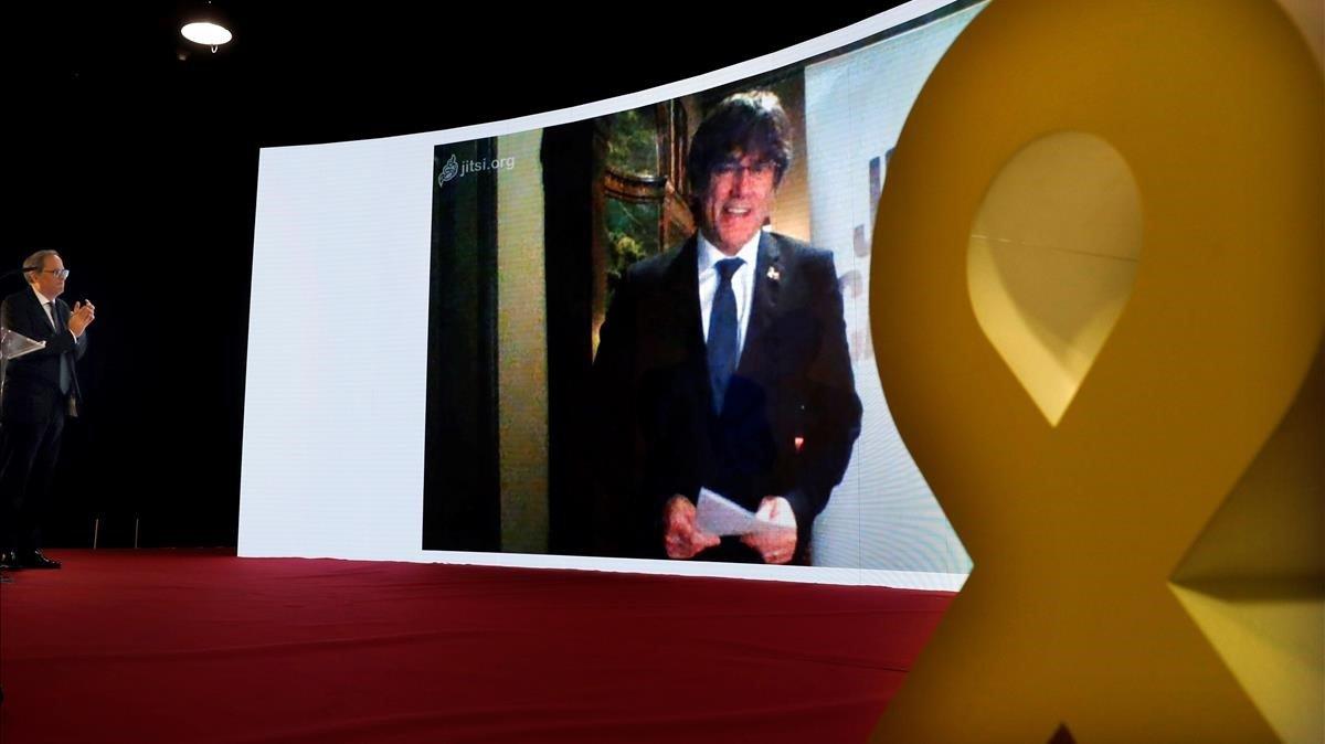 Torra escucha una intervención de Puigdemont por videoconferencia, en el mitin final de campaña de JxCat de las últimas elecciones generales, en Barcelona.