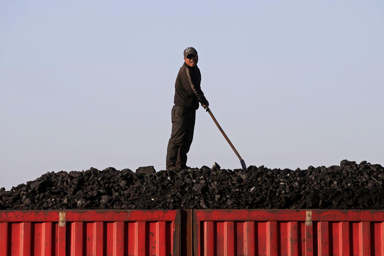 Un trabajador sobe el cargamento de carbón que transporta un tren, en el centro de China.