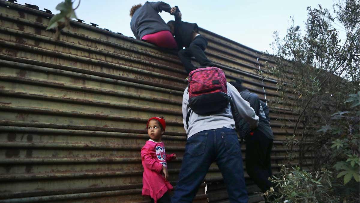 Una familia de migrantes trata de cruzar la frontera en Tijuana.