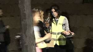 Una joven con chaleco de la organización del Primavera Sound reparte caretas de Puigdemont.