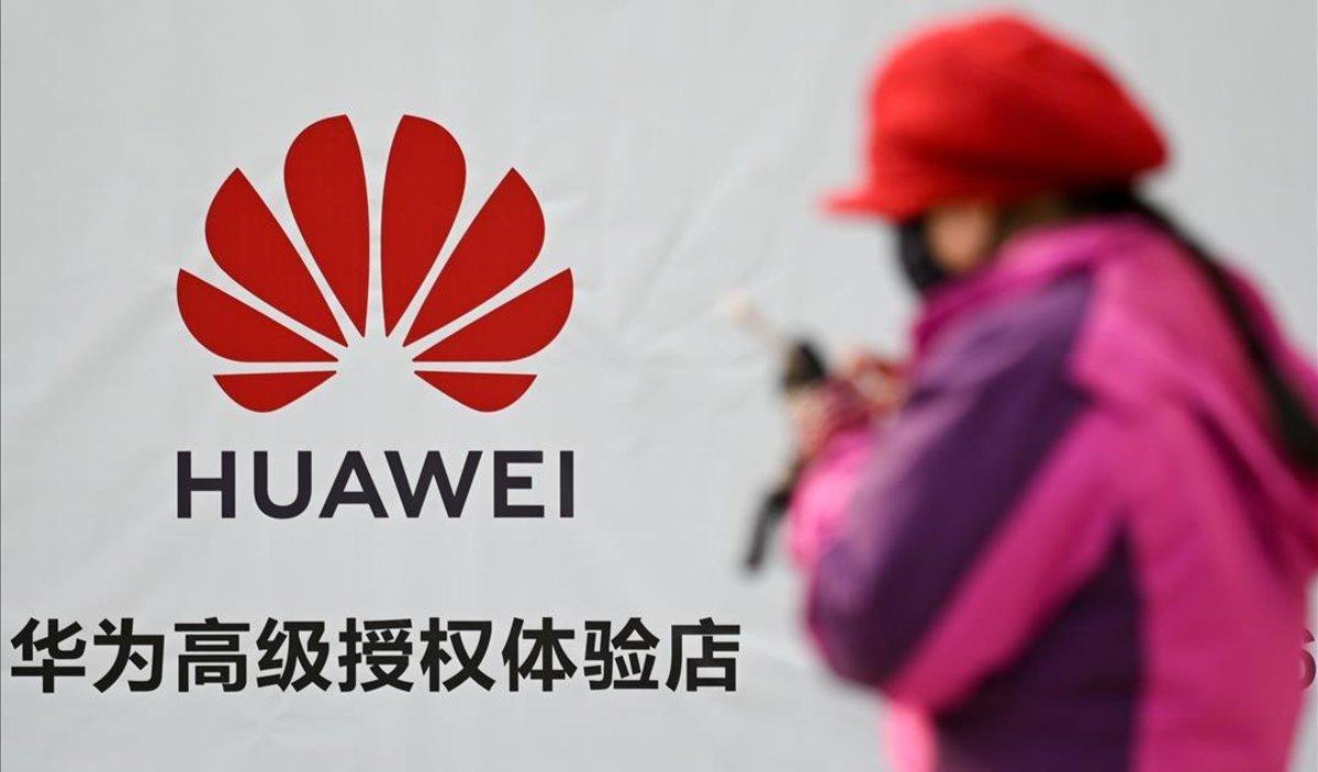 Una mujer consulta su smartphone junto a un cartel publicitario de Huawei, en una calle de Pekín.