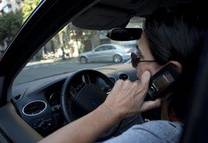 Una mujer habla por teléfono móvil mientras conduce, en una imagen de archivo.