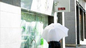 Una mujer pasea protegida con una sombrilla por Lleida este lunes.