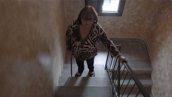 Una mujer que padece esclerosis múltiple sube las escaleras de su casa.
