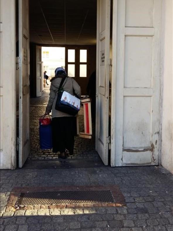 Una refugiada entra con sus pertenencias en el centro de Wilmersdorfer.