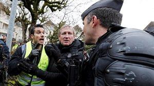 Varios chalecos amarillos forcejean con gendarmes galos mientras aguardan la llegada del presidente frances Emmanuel Macron a un debate con alcaldes de una zona rural del sur este viernes en Souillac.