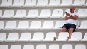 Un hombre espera el inicio de un partido en Tarragona.