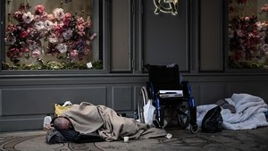 Una persona sin hogar duerme delante de una tienda en París, el pasado abril.
