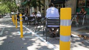 Mesas de una terraza en la calzada, de acuerdo con la regulación excepcional del ayuntamiento, este lunes en la calle de Amigó.