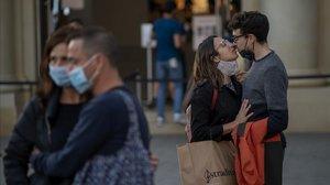 Una pareja con mascarilla se besa en las calles de Barcelona.