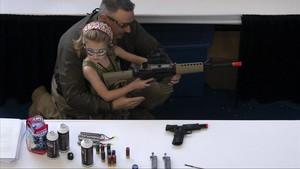 Un hombre muestra a una niña cómo coger una escopeta de aire comprimido durante el NRA Youth Day, en la reunión anual de la NRA, en Houston, en el 2013.