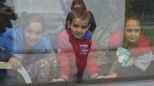 Tres niños refgugiados miran desde dentro de uno de los trenes.