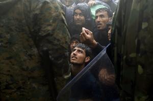 Unos refugiados ruegan a policías macedonios que les dejen pasar.