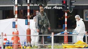Agentes de policíaforense belga investigan el lugar deltiroteo en Lieja.