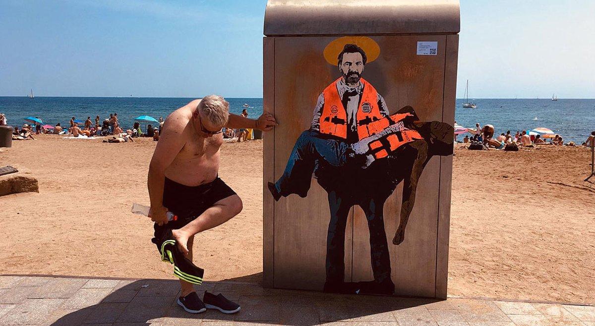 Un bañista se limpia la arena de los pies junto al dibujo de Òscar Camps pintado por Tvboy en la Barceloneta.