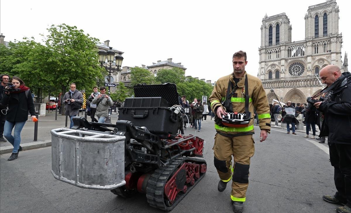 Un bombero, junto con el robot que ayudó a los bomberos en el incendio de Notre Dame, este martes.