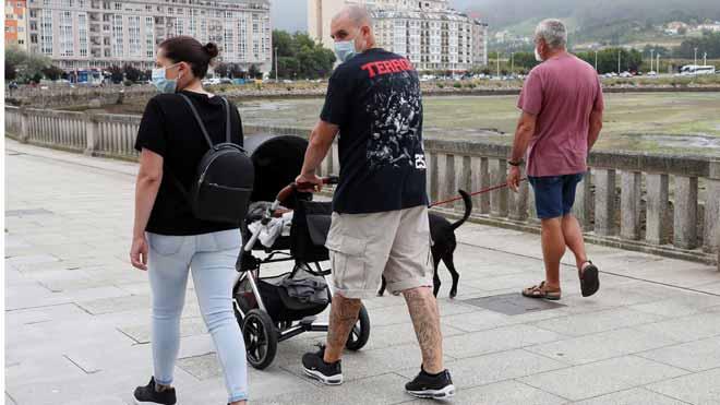 El brote de A Mariña (Lugo) obliga a cerrar cinco días los accesos a la costa. En la foto, paseantes con mascarillas en la localidad de Viveiro.