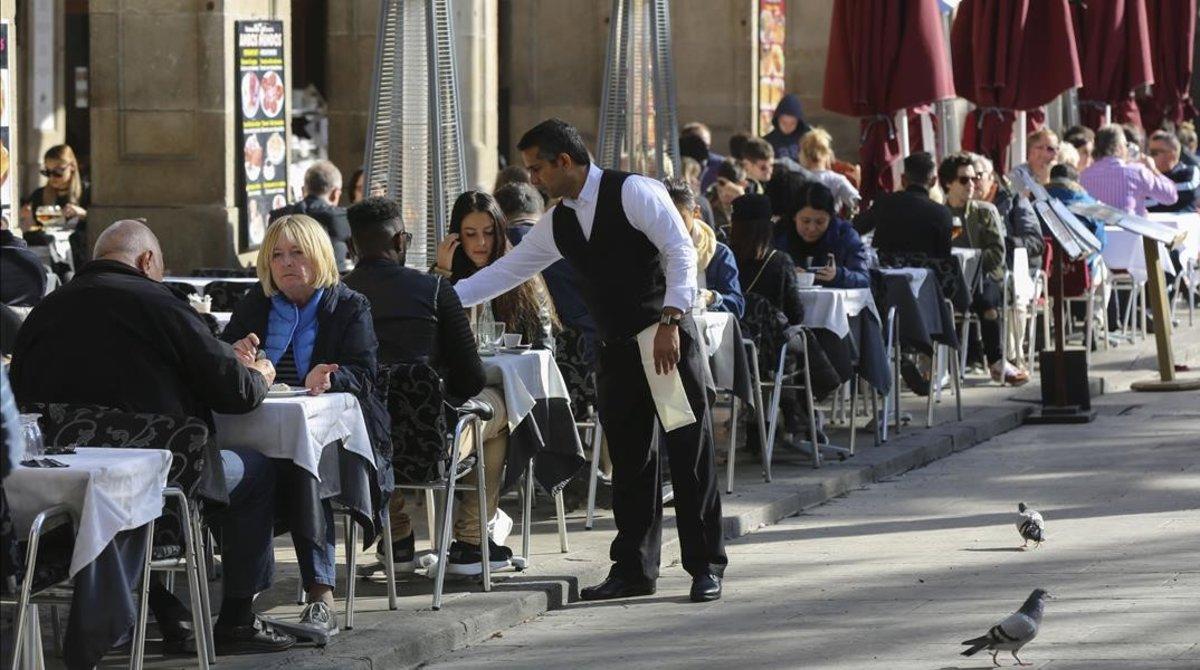 Un camarero sirve unas mesas en un restaurante de la plaza Reial de Barcelona.
