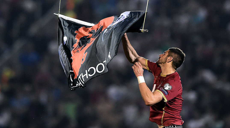El aparato sobrevuela el estadiocon una bandera de la Gran Albania hasta que Stefan Mitrovic logra retirarla.