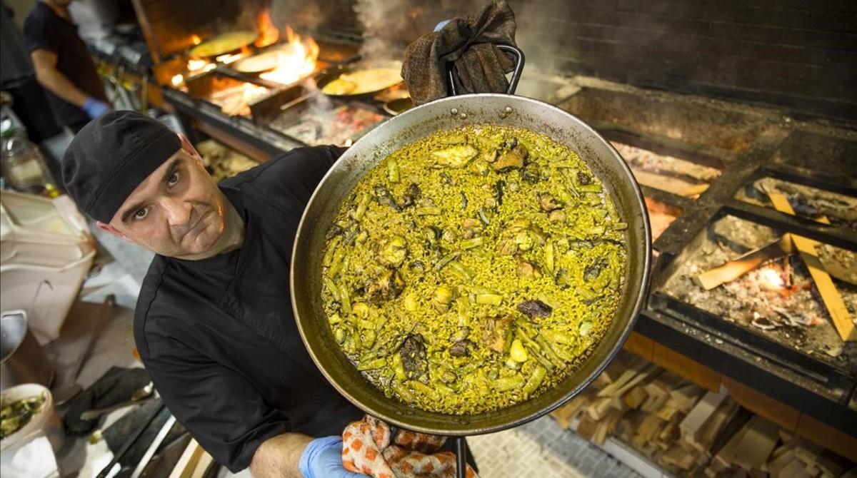Luis, cocinero de Casa Carmela, en València,muestra una paella valenciana.