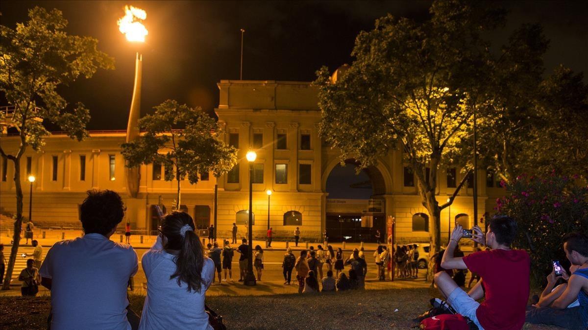 Una pareja observa el fuego en el pebetero, encendido con motivo del 25º aniversario de la inauguración de los Juegos Olímpicos de Barcelona.