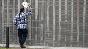 Un hombre habla con un familiar a través de la valla que separa Estados Unidos y México en San Diego, California.