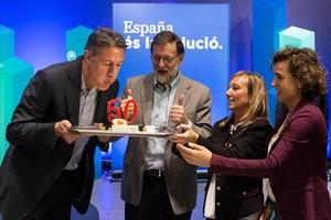 Garcia Albiol sopla las velas del pastel de su cumpleaños, en presencia de Mariano Rajoy, Marisa Xandri, líder del PP de Lleida, y Dolors Montserrat.
