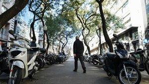 Un hombre caminando en medio de un párking de motos, en Barcelona.