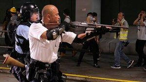 Un oficial de policía de Hong Kong apunta con un arma a los manifestantes.