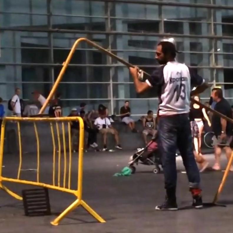 Un hombre improvisa una obra de arte con vallas rotas en la plaza del Macba.