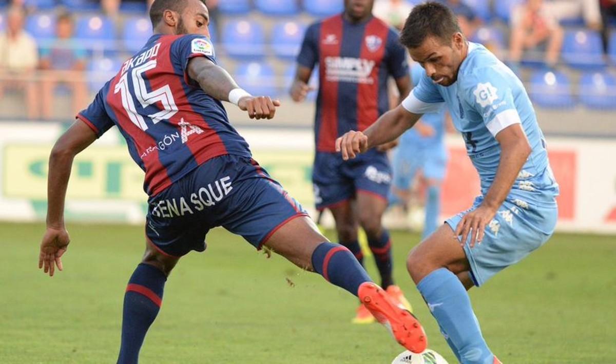 El jugador del Girona, Felipe Sanchón, trata de marcharse del defensa del Huesca, Carlos Akapo.
