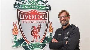Jürgen Klopp posa junto al escudo del Liverpool en las dependencias de la ciudad deportiva de Melwood.
