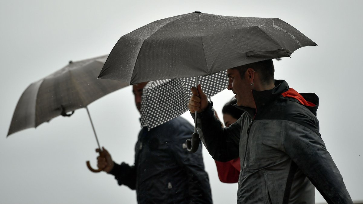 Unas personasse protegen de la lluvia.
