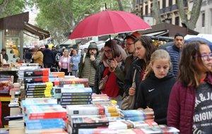 Los primeros visitantes a los puestos callejeros de La Rambla por Sant Jordi.