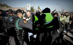 Los taxistas intentan saltar el cordón de la Guarcia Civil para entrar en el puerto de Barcelona.