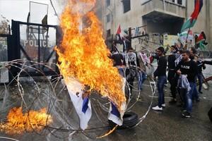 Manifestantes queman una bandera de Israel frente a la embajada de Estados Unidos en Beirut, Líbano.