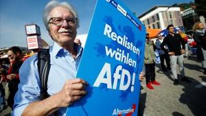 Miembros de AfD protestan en un acto electoral de Merkel, en Happenheim, este viernes.