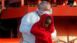 Un miembro de Salvamento Marítimo desembarca en el puerto de Málaga a uno de los menores rescatados en una patera en el Mar de Alborán este martes.