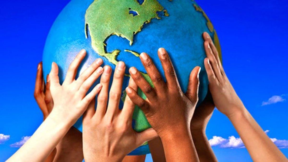 Niños de distintos orígenessostienen una bola del mundo.