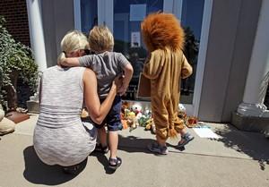Niños lloran la muerte de Cecil, ante la puerta de la clínica del dentista que lo mató, en Bloomington (Minneápolis).