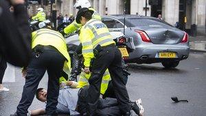 Policías británicos detienen a un manifestante que ha porvocado un accidente en el que se ha visto involucrado el coche del primer ministro Boris Johnson, este miércoles.