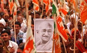 Un granjero sostiene un retrato de Mahatma Gandhi durante una marcha de protesta contra las políticas de industrialización del Gobierno, en Gandhinagar en el estado de Gujarat (India)